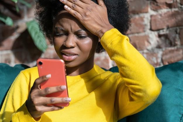 Mulher afro-americana confusa fazendo gesto no rosto com a palma da mão