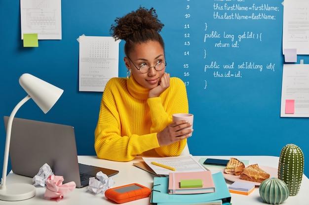 Mulher afro-americana contemplativa bebe cafeína do copo, olha pensativa de lado, vestida de suéter amarelo, usa laptop