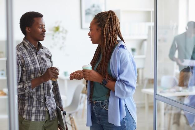 Mulher afro-americana contemporânea conversando com uma jovem colega durante a pausa para o café no escritório