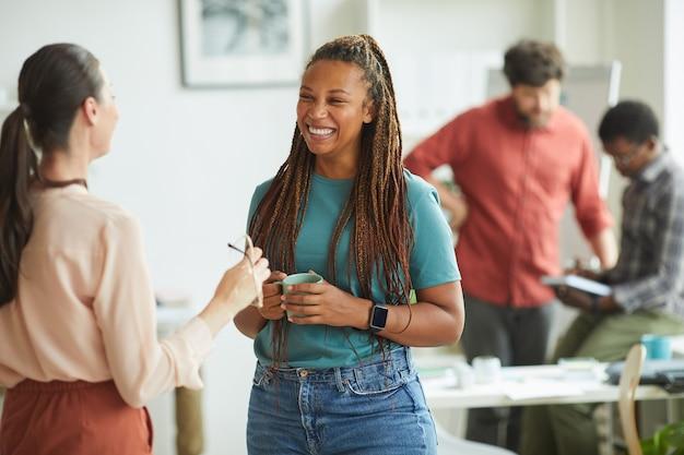 Mulher afro-americana contemporânea sorrindo alegremente enquanto conversava com uma colega durante a pausa para o café no escritório