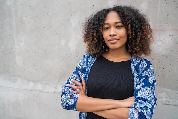 Mulher afro-americana contra parede cinza.