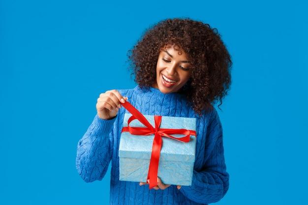 Mulher afro-americana curiosa e feliz, sorridente, garota do dia b de suéter de inverno, puxando o nó atual para desembrulhar o presente e ver o que dentro, comemorando o natal, feriados de ano novo, fundo azul