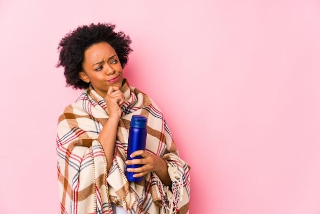 Mulher afro-americana da idade média em um camping isolatedlooking lateralmente com expressão duvidosa e cética.