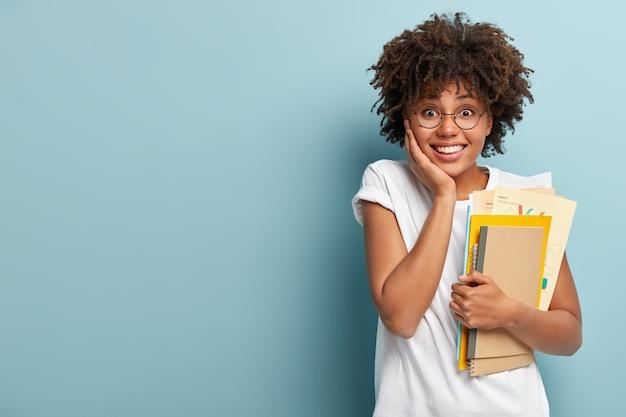 Mulher afro-americana de aparência agradável segura blocos de notas, papéis, estudos na faculdade, feliz por terminar os estudos