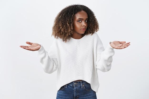 Mulher afro-americana de cabelo encaracolado desavisada dando de ombros, virando o rosto, sacudindo a cabeça, questionada, estendendo as mãos para os lados, não tenho ideia, duvidosa, parede branca