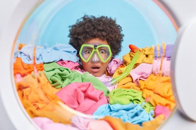 Mulher afro-americana de cabelo encaracolado impressionada olha fixamente maravilhada através de óculos de mergulho enterrados em roupas multicoloridas lavando roupa regularmente