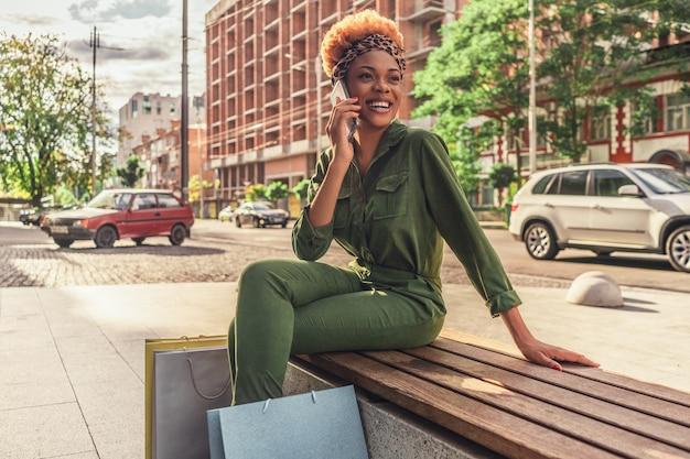 Mulher afro-americana de cabelos cacheados sorridente, sentada em um banco de madeira com sacos de papel enquanto fala no smartphone
