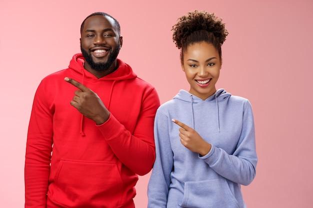 Mulher afro-americana de dois homens sorridente e despreocupada, sorrindo com os dentes brancos se divertindo, brincando, apontando o canto superior esquerdo, mostrando o projeto do casal com orgulho, fundo rosa de pé