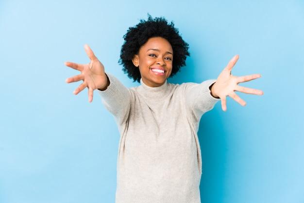 Mulher afro-americana de meia idade contra um azul isolado se sente confiante em dar um abraço para a câmera.