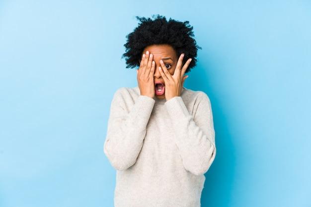 Mulher afro-americana de meia idade contra um blink isolado azul através dos dedos assustados e nervosos.