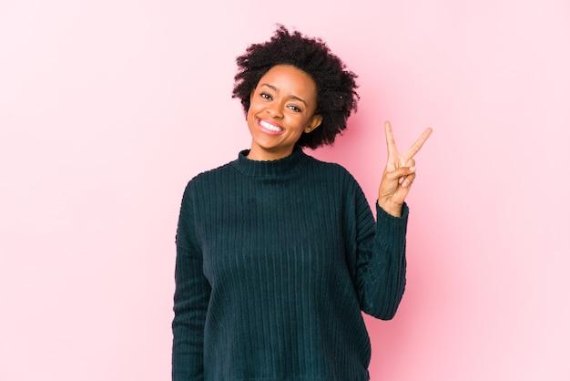 Mulher afro-americana de meia idade contra um rosa isolado alegre e despreocupado, mostrando um símbolo de paz com os dedos.
