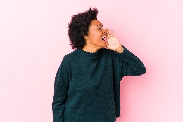 Mulher afro-americana de meia idade contra um rosa isolado gritando e segurando a palma da mão perto da boca aberta.