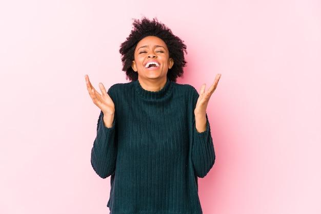 Mulher afro-americana de meia idade contra uma parede rosa isolada alegre rindo muito. conceito de felicidade.