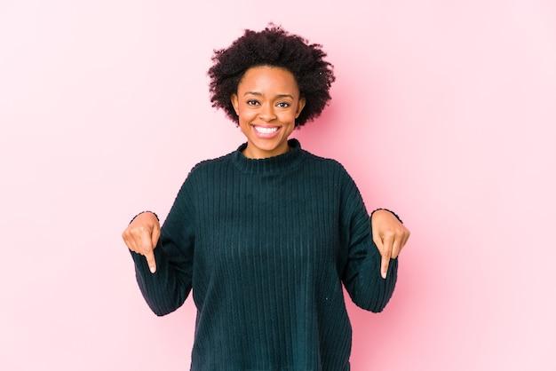Mulher afro-americana de meia idade contra uma superfície rosa isolada aponta para baixo com os dedos, sentimento positivo.