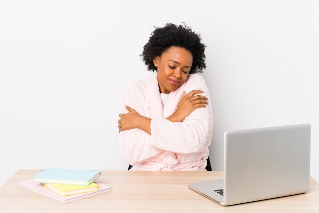 Mulher afro-americana de meia idade trabalhando em casa isolada abraços, sorrindo despreocupada e feliz.