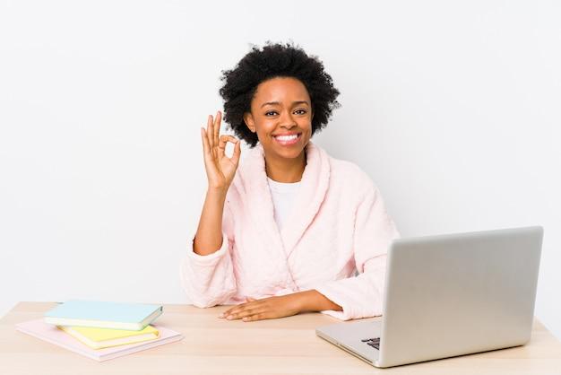 Mulher afro-americana de meia idade, trabalhando em casa, isolada alegre e confiante, mostrando um gesto ok.