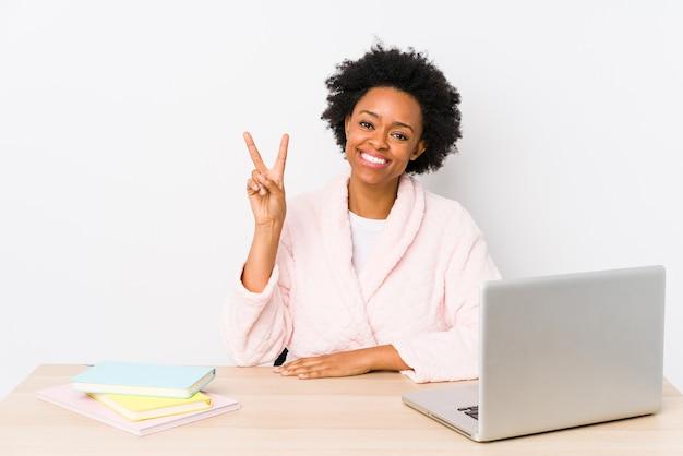 Mulher afro-americana de meia idade trabalhando em casa isolada, mostrando sinal de vitória e sorrindo amplamente.