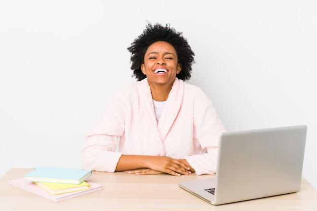 Mulher afro-americana de meia idade trabalhando em casa isolada ri e fecha os olhos, sente-se relaxada e feliz.