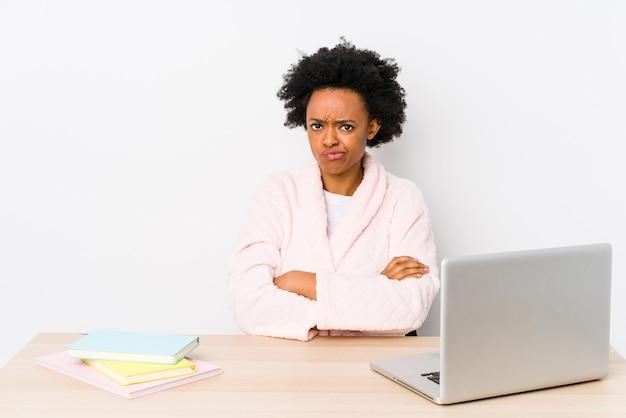 Mulher afro-americana de meia idade, trabalhando em casa, isolada rosto carrancudo em desgosto, mantém os braços cruzados.