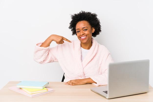 Mulher afro-americana de meia idade trabalhando em casa, pessoa isolada apontando com a mão para um espaço de cópia de camisa, orgulhosa e confiante