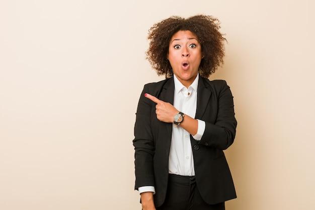Mulher afro-americana de negócios jovem apontando para o lado