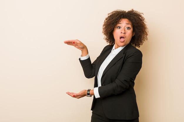 Mulher afro-americana de negócios jovem chocada e espantada, segurando um espaço de cópia entre as mãos.