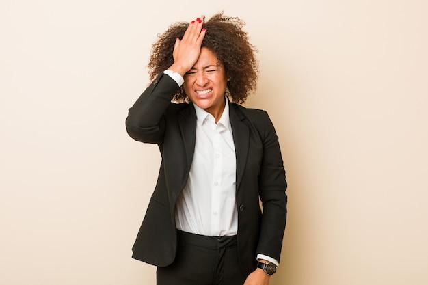 Mulher afro-americana de negócios jovem esquecendo algo, batendo na testa com a palma da mão e fechando os olhos.