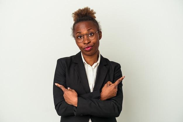 Mulher afro-americana de negócios jovem isolada em pontos de fundo branco para os lados, está tentando escolher entre duas opções.