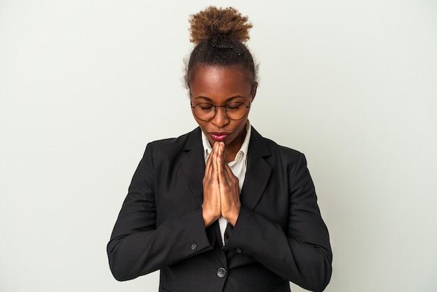 Mulher afro-americana de negócios jovem isolada no fundo branco, de mãos dadas para orar perto da boca, sente-se confiante.
