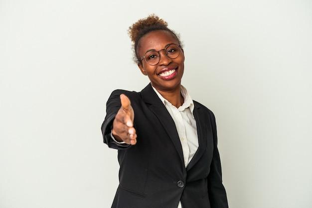 Mulher afro-americana de negócios jovem isolada no fundo branco, esticando a mão na câmera em um gesto de saudação.