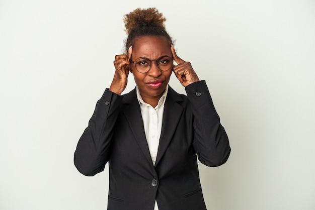 Mulher afro-americana de negócios jovem isolada no fundo branco, focada em uma tarefa, mantendo os indicadores apontando a cabeça.