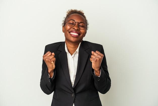 Mulher afro-americana de negócios jovem isolada no fundo branco, levantando o punho, sentindo-se feliz e bem-sucedido. conceito de vitória.