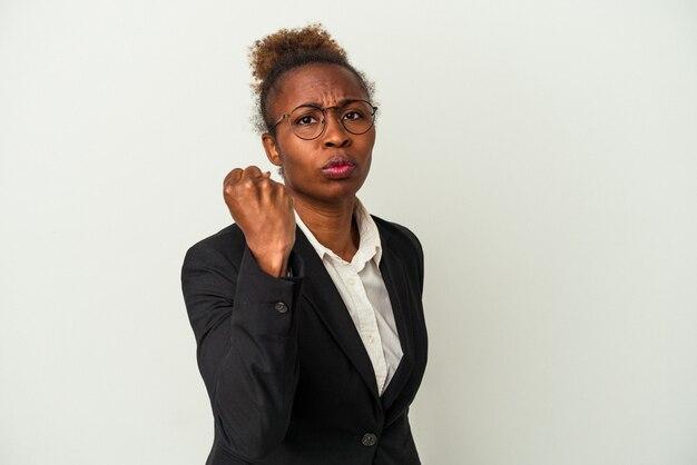 Mulher afro-americana de negócios jovem isolada no fundo branco, mostrando o punho para a câmera, expressão facial agressiva.