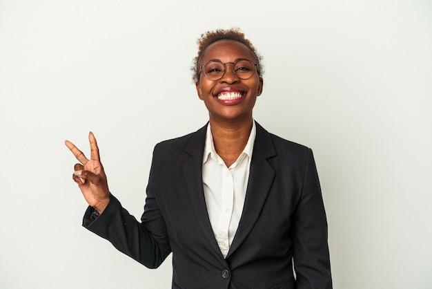 Mulher afro-americana de negócios jovem isolada no fundo branco, mostrando o sinal de vitória e sorrindo amplamente.