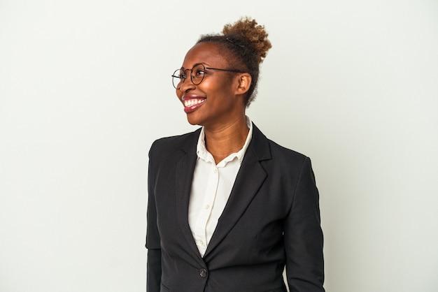Mulher afro-americana de negócios jovem isolada no fundo branco parece de lado sorrindo, alegre e agradável.