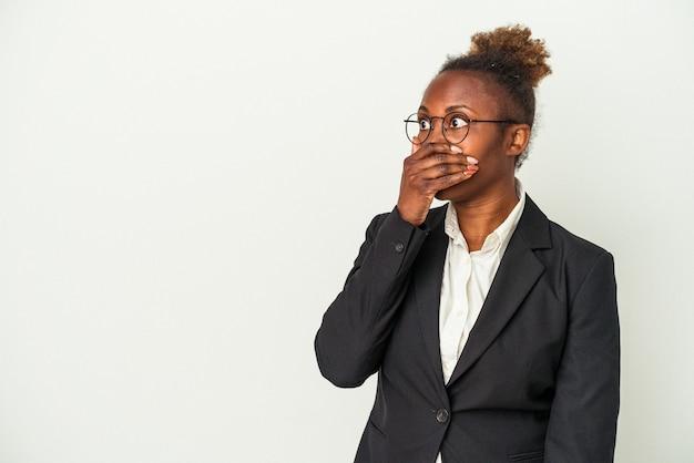 Mulher afro-americana de negócios jovem isolada no fundo branco pensativo, olhando para um espaço de cópia, cobrindo a boca com a mão.
