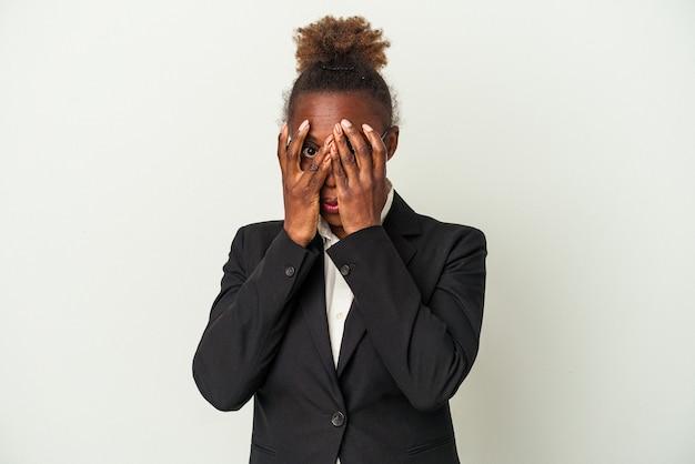 Mulher afro-americana de negócios jovem isolada no fundo branco piscar por entre os dedos assustados e nervosos.