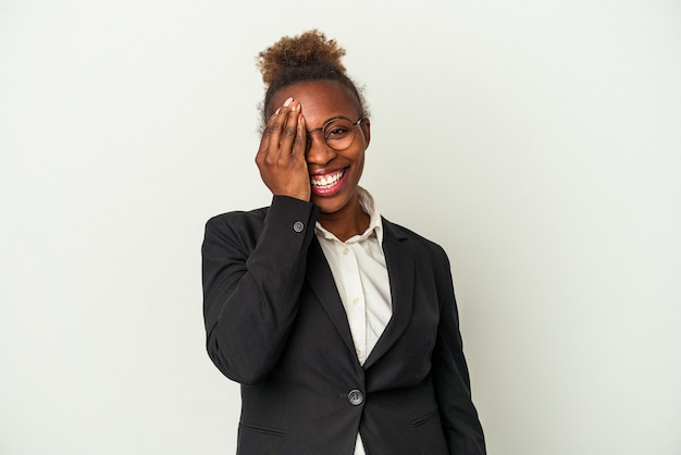 Mulher afro-americana de negócios jovem isolada no fundo branco, se divertindo, cobrindo metade do rosto com a palma da mão.