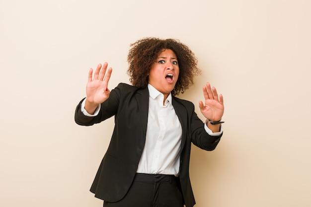 Mulher afro-americana de negócios jovem sendo chocada devido a um perigo iminente