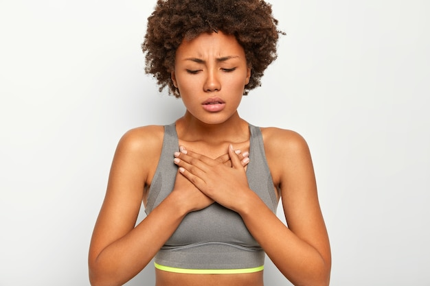Mulher afro-americana de pele escura e frustrada sofre de dores agudas no peito, usa sutiã esportivo cinza, isolado no fundo branco
