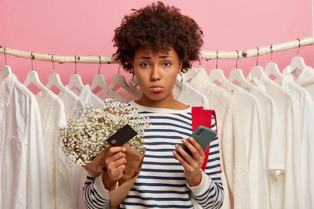 Mulher afro-americana, de pele escura, insatisfeita em pé perto do guarda-roupa com roupas brancas penduradas em cabides, olhando tristemente para a câmera