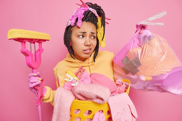 Mulher afro-americana de pele escura insatisfeita olha tristemente para o saco de lixo