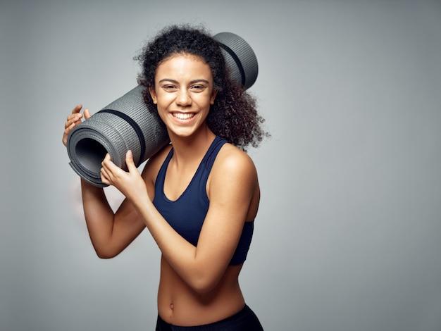 Mulher afro-americana de pele escura, posando em um agasalho e fazendo esportes espaço