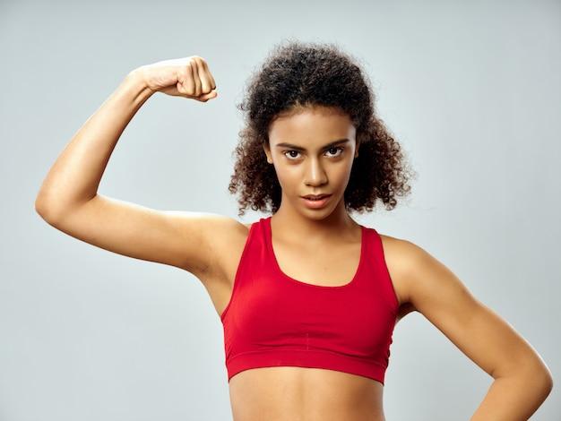 Mulher afro-americana de pele escura, posando em um agasalho e praticando esportes no estúdio