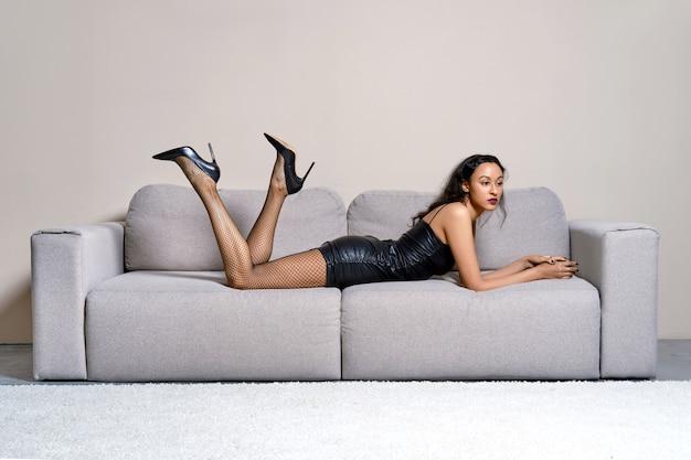 Mulher afro-americana deitada no sofá com um vestido de couro sintético, meia arrastão e pernas arqueadas em salto agulha