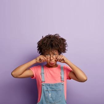 Mulher afro-americana desanimada esfrega os olhos e varre, tem expressão pessimista de pesar, franze o lábio inferior