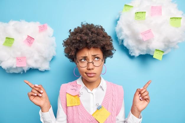 Mulher afro-americana descontente aponta para o lado com uma expressão sem noção e compartilha ideias em post-its coloridos usando óculos redondos poses contra a parede azul