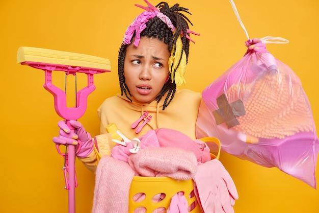 Mulher afro-americana descontente com dreadlocks ocupada fazendo trabalhos domésticos segurando esfregão e lixo