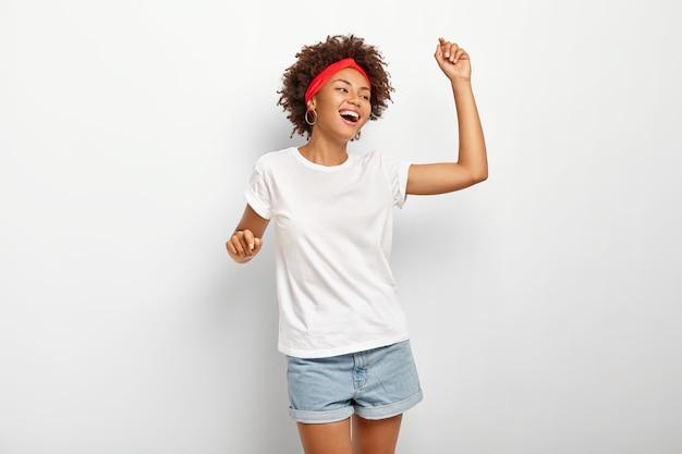 Mulher afro-americana descontraída e alegre se move no ritmo da música favorita, tem olhar alegre, sorri despreocupada