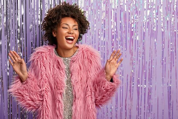 Mulher afro-americana despreocupada e sorridente com maquiagem, cabelos cacheados, dança ativamente, vestida com um casaco de pele rosa